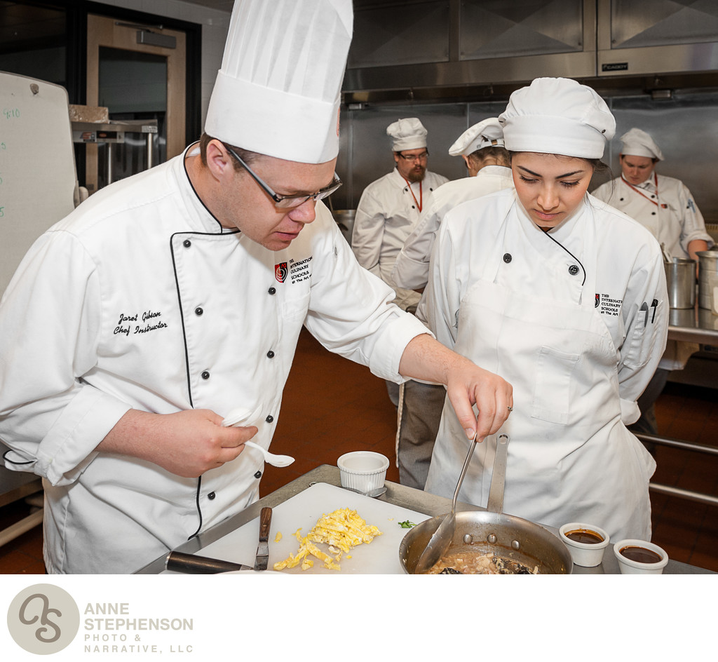 Chef trains culinary student in preparing Asian food