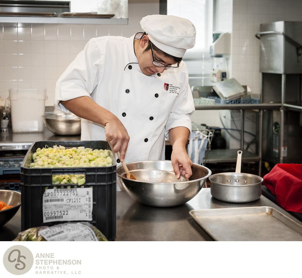Culinary student stirs a stainless steel bowl