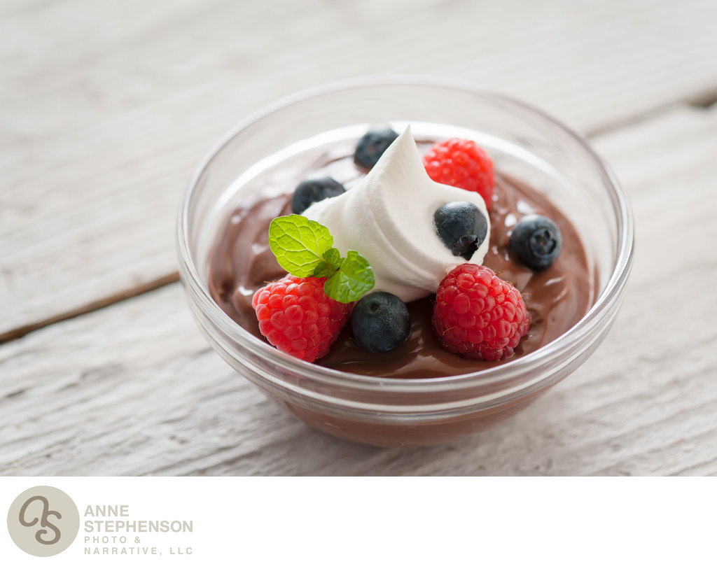 Chocolate pudding berry bowl with dollop of cream.