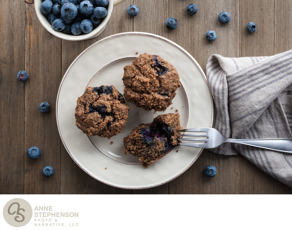 blueberry muffins on a plate with napkin and fork