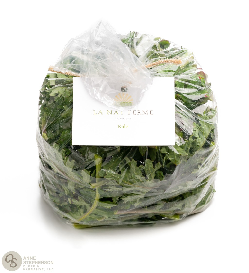 Closed and tied bag of purple kale on white