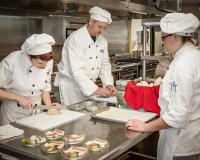 Students prepare restaurant food in cooking class