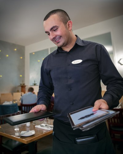 Waiter delivers menu with a smile at Greek restaurant