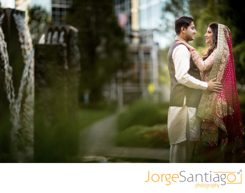 slightly blurred outdoor shot of south asian bride and groom