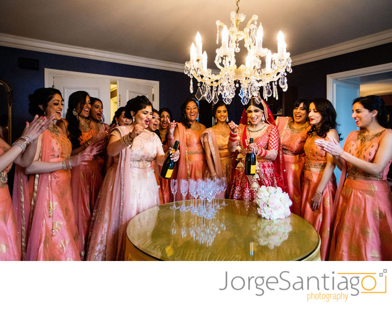 south asian bride popping champaign with bridesmaids in pink gowns