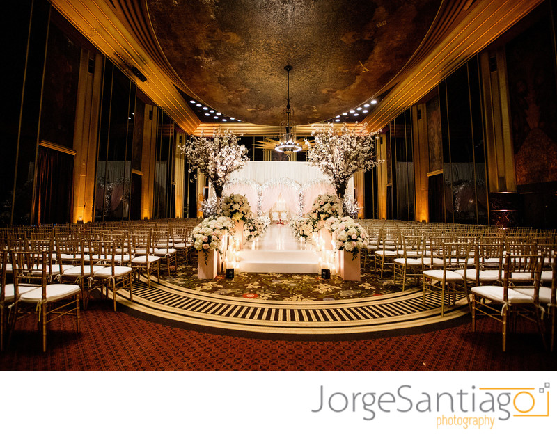 elaborate flower and candle stage in elegent venue with gold accents