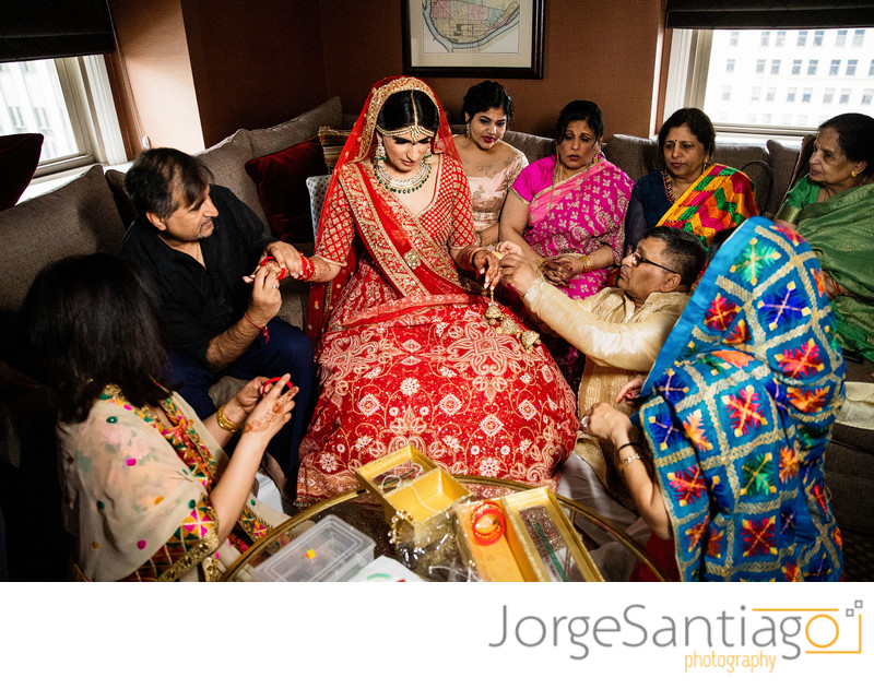 south asian indian bride dressed in red receiving gifts from family