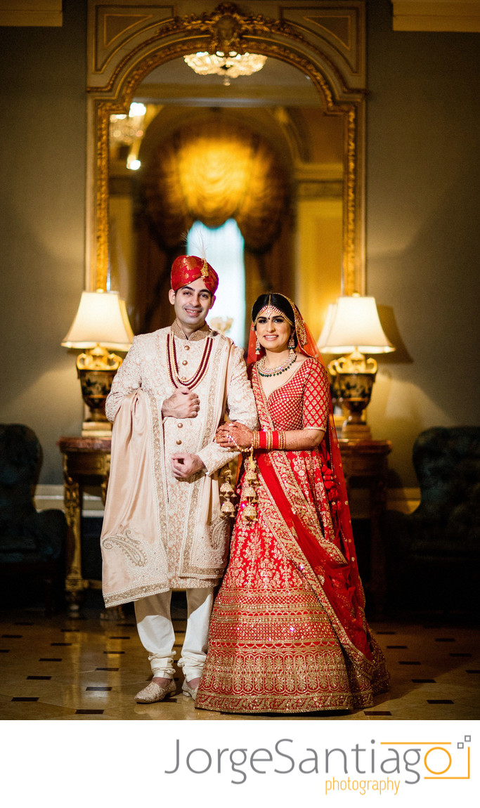 south asian bride and groom standing in front of elaborate mirror smiling